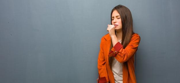 Jonge natuurlijke vrouw hoestend, ziek door een virus of infectie