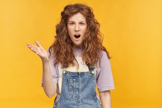 Jonge negatieve vrouw, draagt blauwe overall en paars t-shirt, steekt haar hand op met een ongelukkige, gekke gezichtsuitdrukking, houdt haar mond wijd open