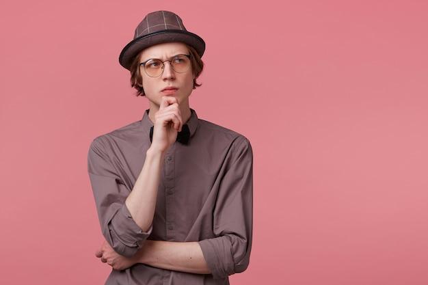 Jonge, netjes geklede man staat met zijn hand op een kin, kijkt zorgvuldig rechtsboven, serieus, denkt na over een probleem, denkt na over wat literatuur, op roze achtergrond