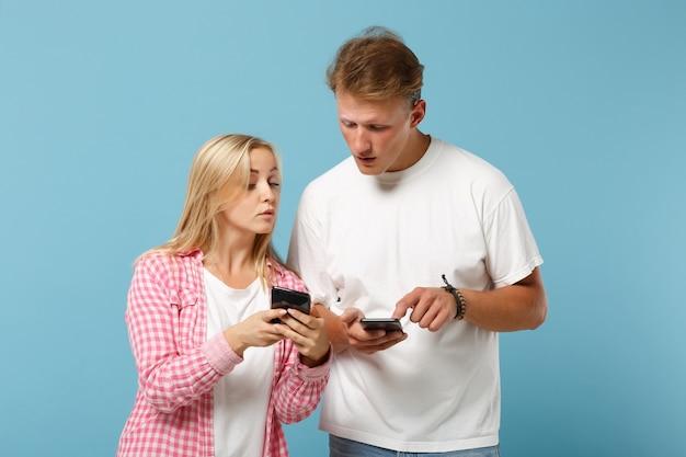 Jonge nieuwsgierige paar vrienden man en vrouw in wit roze lege lege t-shirts poseren