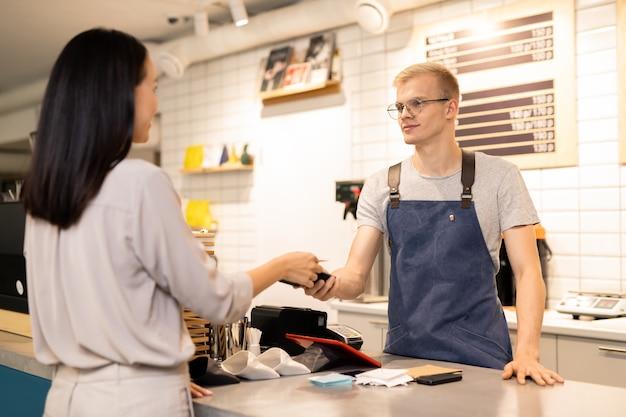 Jonge ober die elektronische betalingsmachine over balie houdt terwijl een van de klanten met een creditcard betaalt voor haar bestelling