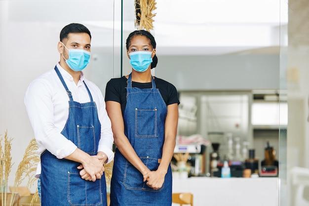 Jonge ober en serveerster in medische maskers en schorten die zich bij ingang van kleine bakkerij bevinden Premium Foto