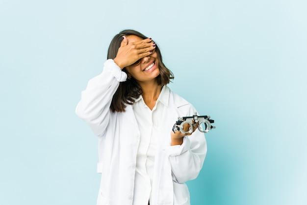 Jonge oculist latijns-vrouw bedekt ogen met handen, glimlacht breed wachtend op een verrassing.