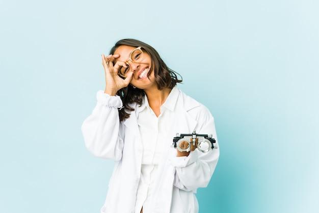 Jonge oculist latijns-vrouw over geïsoleerde muur die ok teken over ogen toont