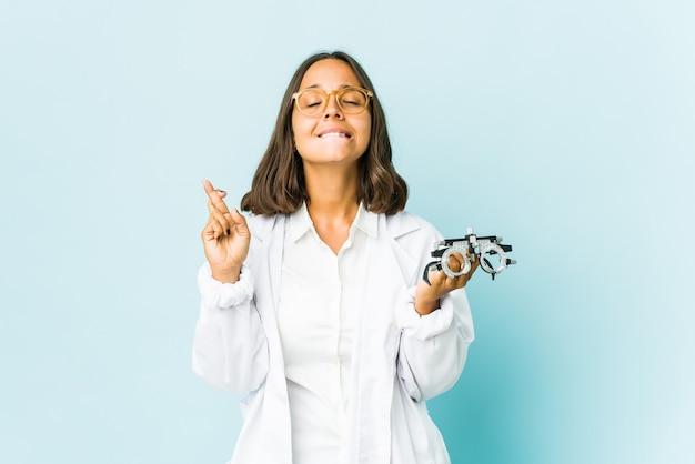 Jonge oculist latijns-vrouw over geïsoleerde muur die vingers kruisen voor het hebben van geluk