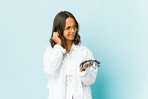Jonge oculistvrouw over geïsoleerde muur die oren bedekt met vingers, gestrest en wanhopig door een luide omgeving