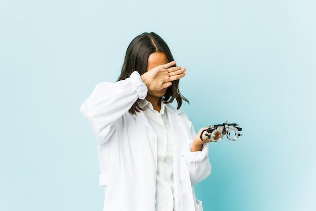 Jonge oculistvrouw over geïsoleerde muur die twee gekruiste wapens houdt, ontkenningsconcept