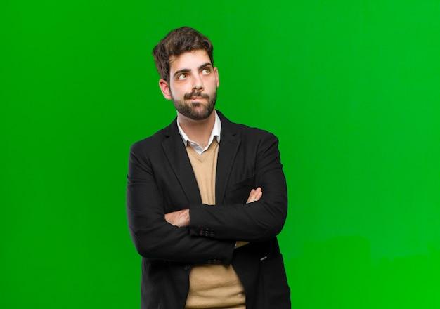 Jonge of zakenman die, lip bijten en onzeker en nerveus voelen twijfelen, kijkend om ruimte aan de kant op groen te kopiëren