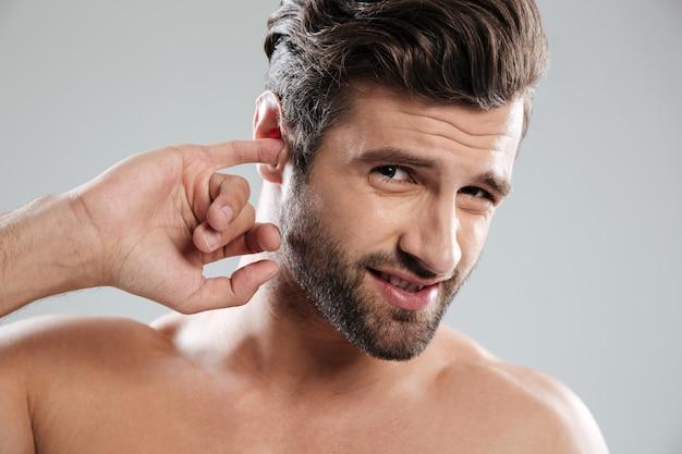 Jonge onbeleefde man zijn oor plukken