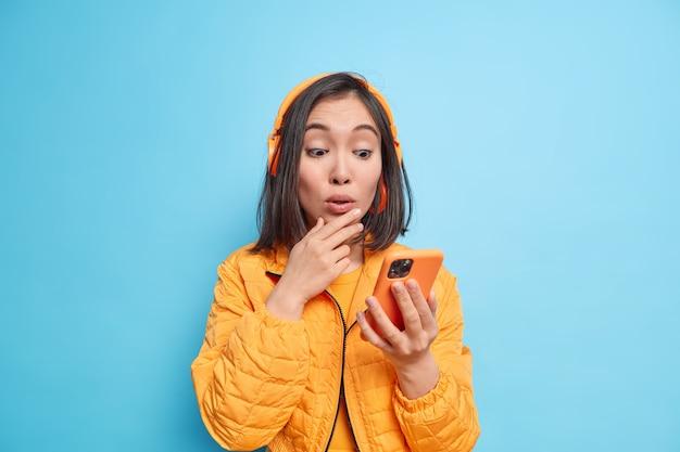 Jonge onder de indruk aziatische vrouw gericht op smartphone luistert muziek via koptelefoon reageert op iets geweldigs gekleed in stijlvolle oranje jas geïsoleerd over blauwe muur. moderne technologie