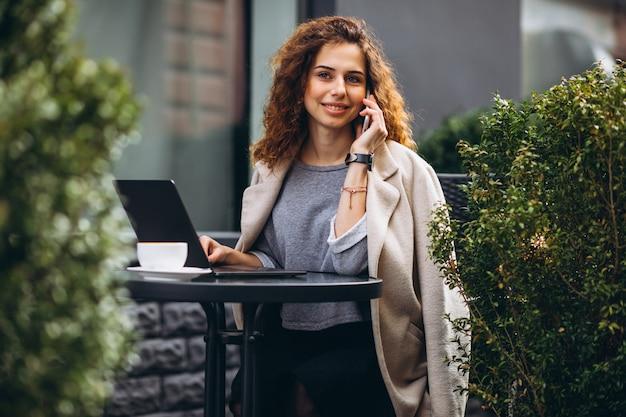 Jonge onderneemster die aan een computer buiten het koffie werkt