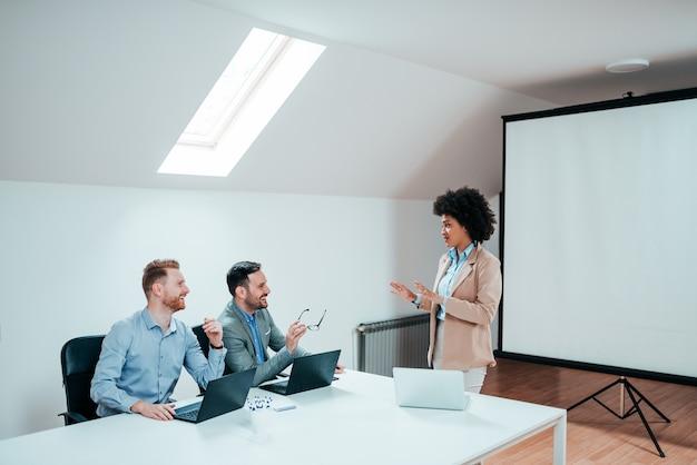 Jonge onderneemster die aan twee zakenlieden in een vergaderzaal voorstellen.
