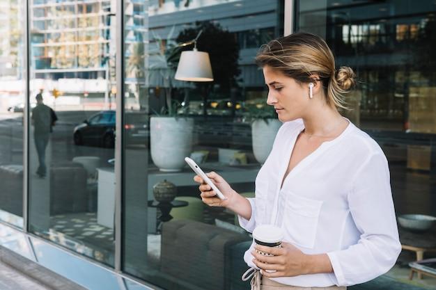 Jonge onderneemster die beschikbare koffiekop houden die mobiele telefoon met behulp van