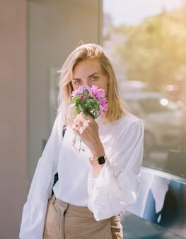 Jonge onderneemster die de bloemen ruikt die in hand houden en aan camera kijken