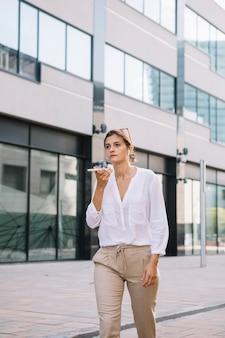 Jonge onderneemster die dichtbij het bureaugebouw loopt dat op mobiele telefoon spreekt