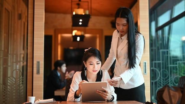 Jonge onderneemster die enkele nieuwe ideeën over project geeft aan haar partners in vergaderruimte.