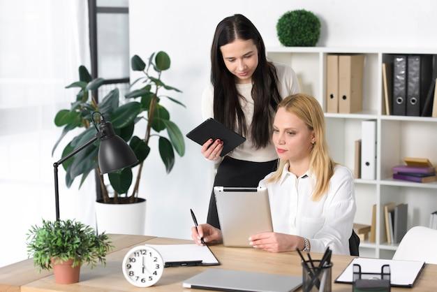 Jonge onderneemster die iets op digitale tablet toont aan haar collega in het bureau