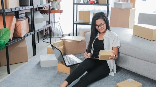 Jonge onderneemster die laptop het werk thuis met behulp van