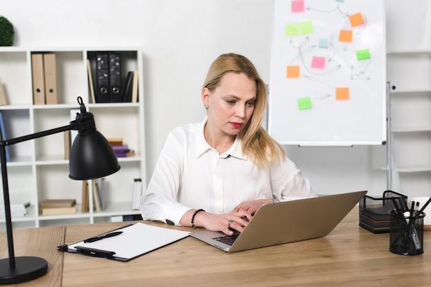 Jonge onderneemster die laptop in het bureau met behulp van