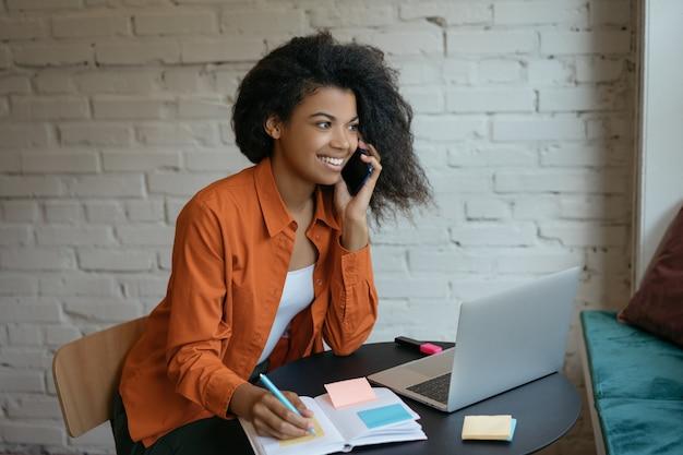 Jonge onderneemster die laptop met behulp van, sprekend op mobiele telefoon, die nota's neemt, opstarten start