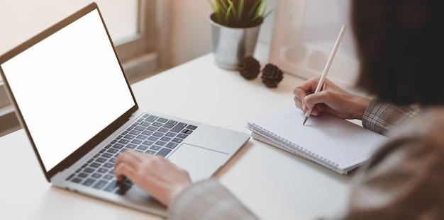 Jonge onderneemster die laptop typen en haar idee schrijven