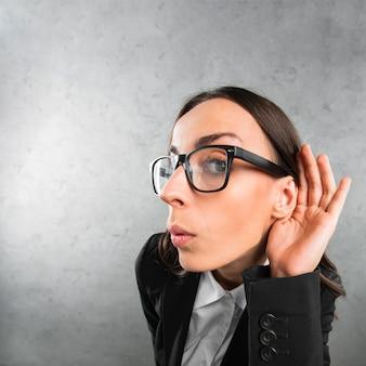 Jonge onderneemster die met haar hand op een oor tegen grijze achtergrond luistert