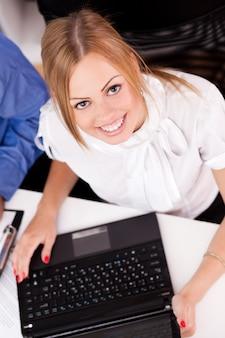 Jonge onderneemster die met laptop werkt