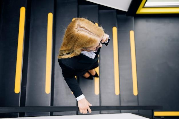 Jonge onderneemster die mobiele telefoon met behulp van terwijl de treden in bureau beklimt