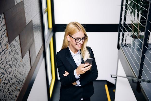 Jonge onderneemster die mobiele telefoon met behulp van terwijl stijgt onderaan de treden in bureau