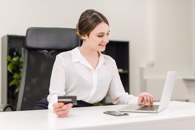 Jonge onderneemster die online betalingen maakt die creditcard en internet op laptop in het bureau gebruiken