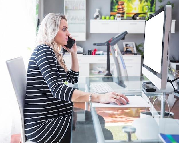 Jonge onderneemster die op cellphone in bureau spreekt
