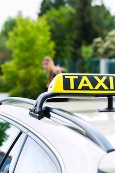Jonge onderneemster die op een taxi wacht die de bestuurder tegenhoudt die vanaf de stoep zwaait