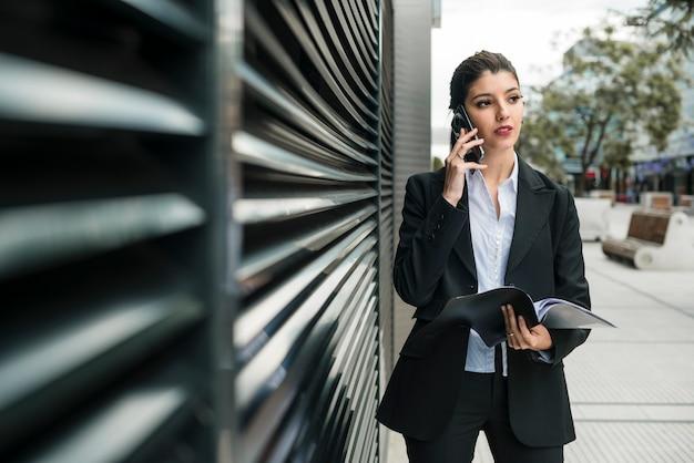 Jonge onderneemster die op mobiele holdingsomslag van de telefoonholding in de weg kijkend spreken