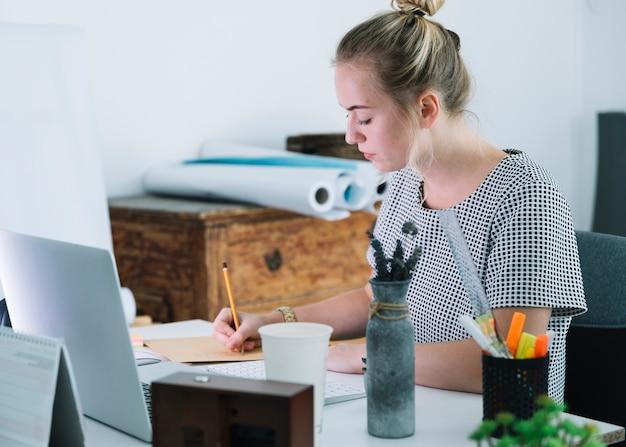Jonge onderneemster die op papier over het bureau schrijft
