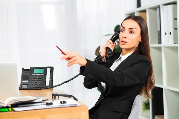 Jonge onderneemster die op telefoon spreekt die potlood richt op ergens