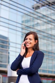 Jonge onderneemster die over de mobiele telefoon in fron van de bureaubouw spreekt