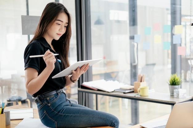 Jonge onderneemster die tablet gebruiken die informatie zoeken die online op de markt brengen.