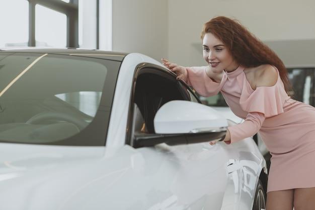 Jonge onderneemster die voor nieuwe auto bij het handel drijventoonzaal winkelen