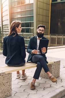 Jonge onderneemster die zakenman bekijken die digitale tabletzitting op bank gebruiken