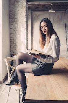 Jonge onderneemster gezet op een lijst die een boek leest