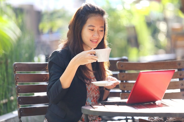 Jonge onderneemster in openlucht gebruikend laptop en drinkend koffie.