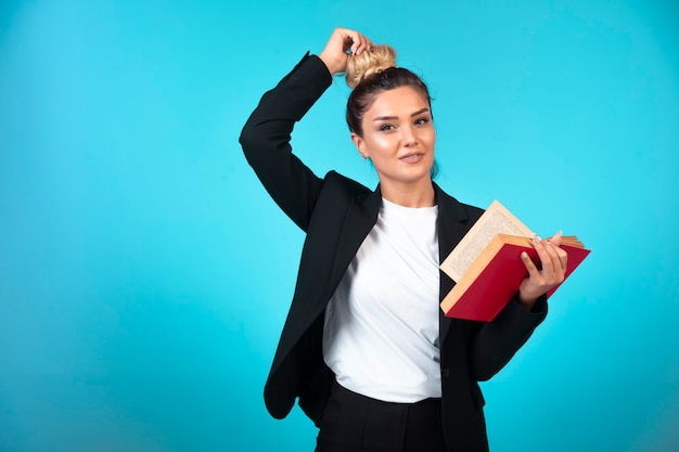 Jonge onderneemster in zwarte blazer die een taakboek houdt en haar broodje controleert.