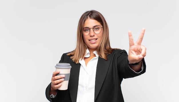 Jonge onderneemster met een koffie die gelukkig, zorgeloos en positief glimlacht en kijkt, overwinning of vrede met één hand gebaart
