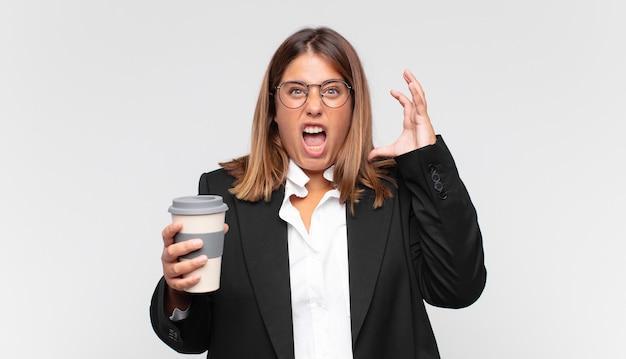 Jonge onderneemster met een koffie die met handen in de lucht gilt, zich woedend, gefrustreerd, gestrest en van streek voelt