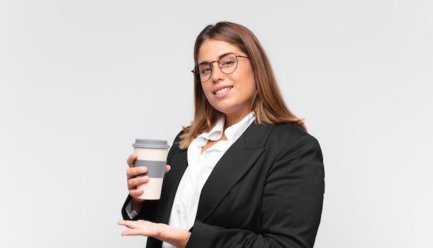 Jonge onderneemster met een koffie die vrolijk glimlacht, zich gelukkig voelt en een concept in exemplaarruimte met handpalm toont