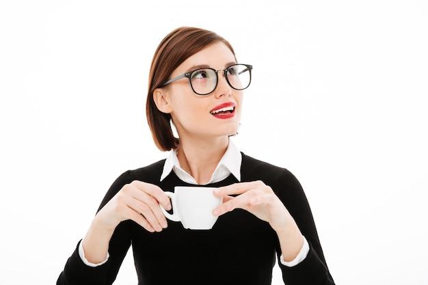 Jonge onderneemster met koffie of theekop en laptop computer