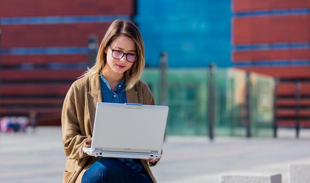 Jonge onderneemster met laptop computer bij stedelijke openlucht.