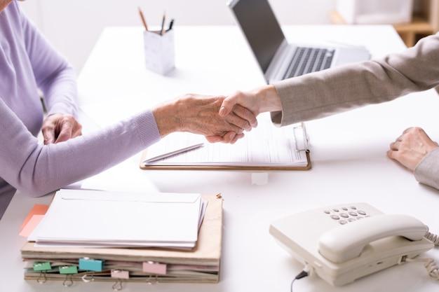 Jonge onderneemster of agent die de hand van hogere cliënt of partner schudt over bureau en ondertekende documenten tijdens het maken van overeenkomst