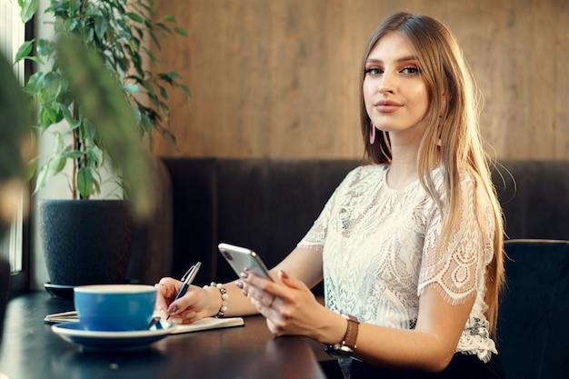 Jonge onderneemsterzitting bij de lijst in een koffiewinkel en het maken van nota's