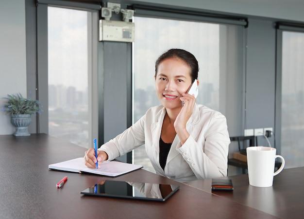 Jonge onderneemsterzitting bij de lijst op werkplaats in bureau die de telefoon met behulp van